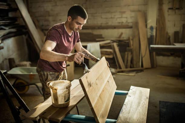 joven pintando la madera